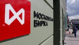 Люди проходят мимо здания Московской биржи 26 мая 2017 года. Российские фондовые индексы слегка отскочили в пятницу после масштабных распродаж и принудительного закрытия позиций предыдущих дней, породив надежды на достижение рынком локального дна. REUTERS/Segrei Karpukhin