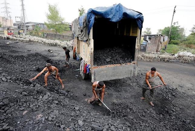 6月16日、新日鉄住金が原料炭価格をスポット価格(インデックス)基準に変更することは、売り手である資源メジャーの寡占化に加え、買い手となる鉄鋼業界における中国やインドの台頭という大きな環境変化を反映している。写真は石炭をトラックに積む作業員たち。インドのジャムで4月撮影(2017年 ロイター/Mukesh Gupta)