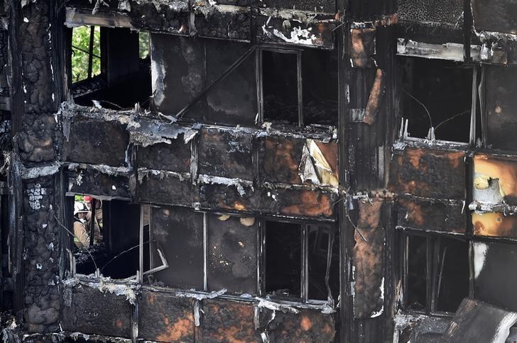 Firefighters at the Grenfell Tower block which was destroyed in a disastrous fire, in north Kensington, West London, Britain June 16, 2017.   REUTERS/Hannah McKay