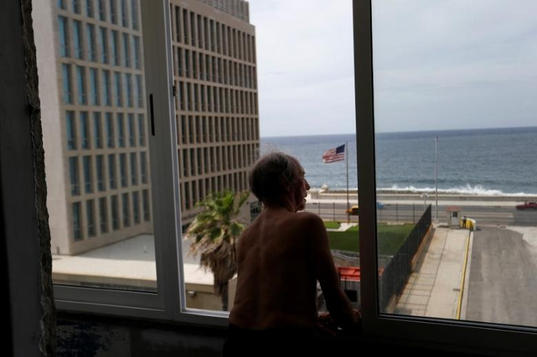 A man looks out of the window of his apartment across from the U.S. embassy in Havana, Cuba June 13, 2017. REUTERS/Stringer