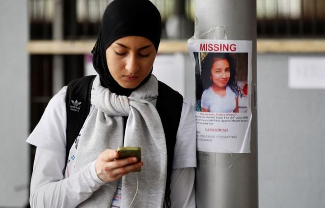 A woman stands by a missing person poster near The Grenfell Tower block, destroyed by fire, in north Kensington, West London, Britain June 16, 2017. REUTERS/Stefan Wermuth