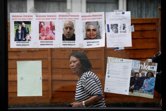 A woman walks by missing person posters near The Grenfell Tower block, destroyed by fire, in north Kensington, West London, Britain June 16, 2017. REUTERS/Stefan Wermuth