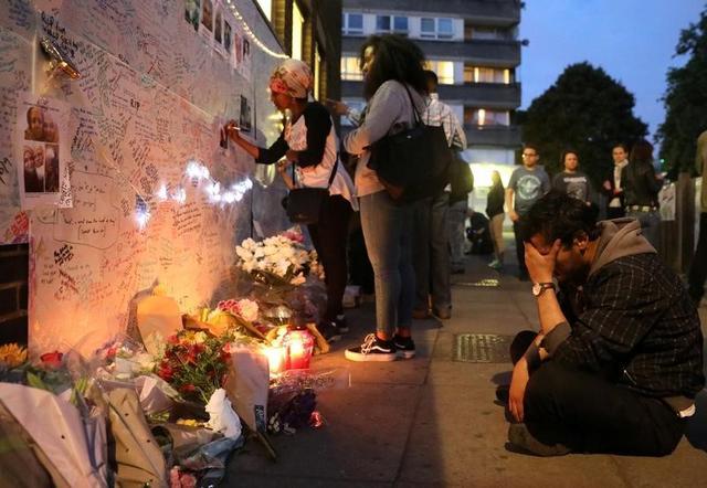 6月15日、大規模火災で黒焦げの無残な姿をさらすロンドンの高層住宅周辺では、はっきりと怒りの声が上がっていた。地元当局が、富裕層を優遇する政策に走り、貧しい市民の安全や福利を軽視している、というのだ。写真は被災者へのメッセージを現場近くの壁に書き込む市民 (2017年 ロイター/Paul Hackett)