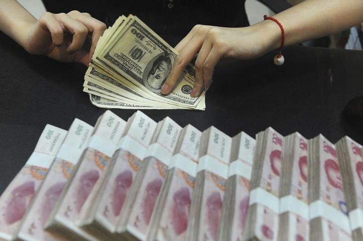 资料图片:2010年9月,合肥,一家银行的柜员在清点美元纸币。REUTERS/Stringer