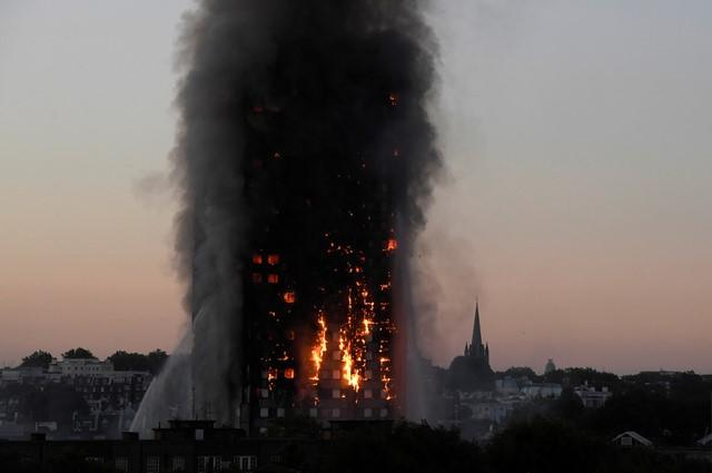 Flames and smoke billow as firefighters deal with a serious fire in the Grenfell Tower apartment block at Latimer Road in West London, Britain June 14, 2017. REUTERS/Toby Melville/Files