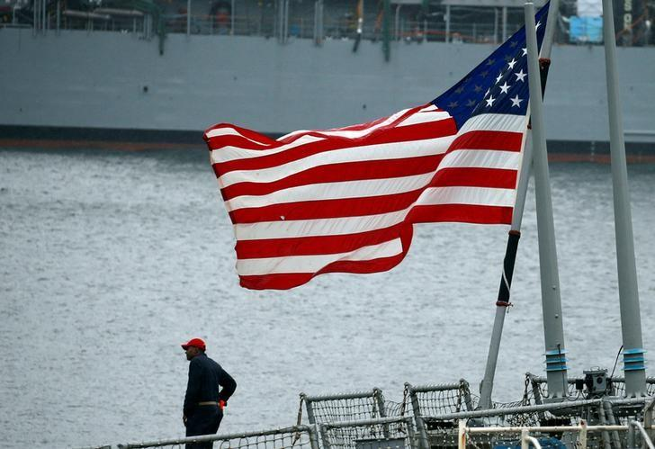 A member of the U.S. Navy Damage Control Training Team is seen near the U.S. national flag on the Arleigh Burke-class guided-missile destroyer USS Fitzgerald, which has been damaged from colliding with a Philippine-flagged merchant vessel, at the U.S. naval base in Yokosuka, south of Tokyo, Japan June 18, 2017. REUTERS/Toru Hanai