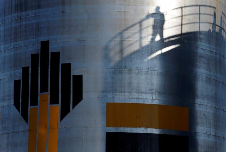 FILE PHOTO: The shadow of a worker is seen besdide the logo of the Rosneft oil company at an oil field in Russia, August 4, 2016. REUTERS/Sergei Karpukhin/File Photo