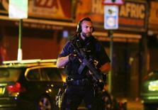 """Un policía armado vigila el lugar donde un vehículo arrollo a personas en el barrio de Finsbury Park en Londres. 19 de junio de 2017. Varias personas resultaron heridas en la madrugada del lunes luego de que una camioneta atropelló a fieles que salían de una mezquita en el norte de Londres, dijeron testigos, en un evento que la policía británica describió como """"un incidente importante"""".  REUTERS/Neil Hall"""