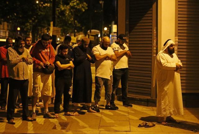6月19日、複数の目撃者によるとロンドン北部のフィンズベリー・パークで未明、1台のバンがモスクを訪れていた信者たちに突っ込み、数人の負傷者が出ている。写真は現場付近で祈りを捧げる人々(2017年 ロイター/Neil Hall)