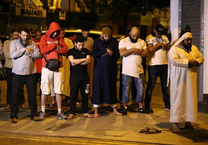 Men pray after a vehicle collided with pedestrians near a mosque in the Finsbury Park neighborhood of North London, Britain June 19, 2017. REUTERS/Neil Hall