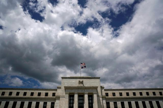 FILE PHOTO: Flags fly over the Federal Reserve Headquarters on a windy day in Washington, U.S., May 26, 2017. REUTERS/Kevin Lamarque
