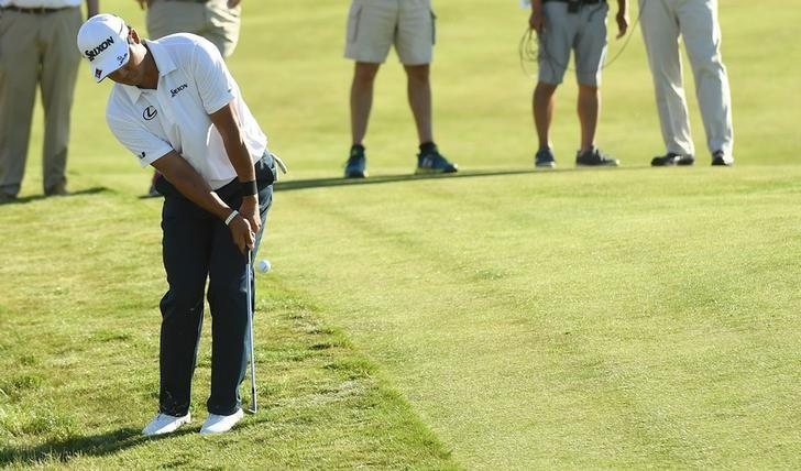 Jun 18, 2017; Erin, WI, USA; Hideki Matsuyama chips up onto the 18th green during the final round of the U.S. Open golf tournament at Erin Hills. Mandatory Credit: Michael Madrid-USA TODAY Sports