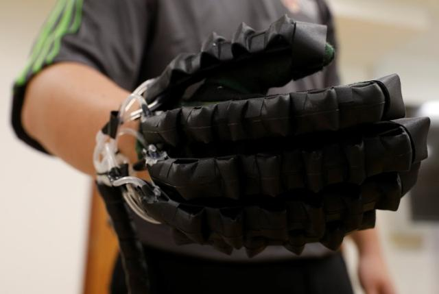 An National University of Singapore (NUS) researcher shows a fabric-based soft robotic glove at NUS in Singapore June 8, 2017. Picture taken June 8, 2017. REUTERS/Edgar Su