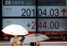 Электронное табло в Токио, демонстрирующее показатели индекса Nikkei.  Японские акции достигли двухнедельных пиков в понедельник на фоне укрепления доллара к иене, в то время как бумаги Nomura Real Estate снизились после сообщения о том, что Japan Post больше не рассматривает покупку доли в девелопере. REUTERS/Toru Hanai