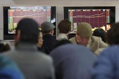 """Инвесторы в Шанхае смотрят на экраны с информацией о торгах. Китайский фондовый рынок закрылся ростом в понедельник, при этом индекс """"голубых фишек"""" CSI300 прервал трехдневную серию потерь на фоне признаков улучшения ситуации с ликвидностью, а также поскольку рынок ждет меньшего числа IPO.  REUTERS/Aly Song (CHINA - Tags: BUSINESS)"""