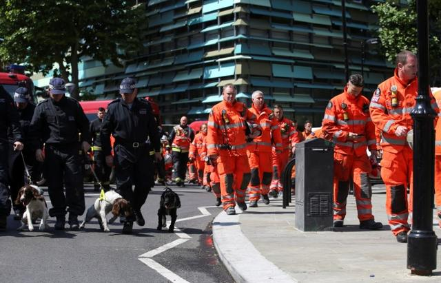 Members of the emergency services arrive to attend a minute's silence for the victims of the Grenfell Tower fire near the site of the blaze in North Kensington, London, Britain, June 19, 2017. REUTERS/Marko Djurica