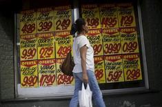 Consumidora passa por cartazes com preços de produtos do lado de fora de um mercado no Rio de Janeiro. 09/12/2017 REUTERS/Ricardo Moraes