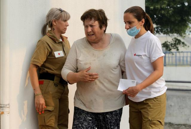 A woman is attended by Red Cross workers outside a relief centre for people affected by a forest fire in Figueiro dos Vinhos, Portugal, June 19, 2017. REUTERS/Miguel Vidal