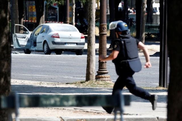 A French gendarme runs past a car on the Champs Elysees avenue after an incident in Paris, France, June 19, 2017.   REUTERS/Charles Platiau