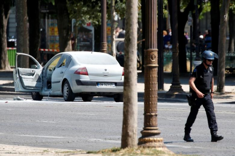 A French gendarme walks past a burned car on the Champs Elysees avenue after an incident in Paris, France, June 19, 2017 . REUTERS/Charles Platiau