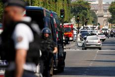 شرطيون فرنسيون يؤمنون المنطقة التي تحيط سيارة مدمرة في جادة الشانزليزيه بعد واقعة في باريس يوم الاثنين. تصوير: جونزالو فوينتس - رويترز