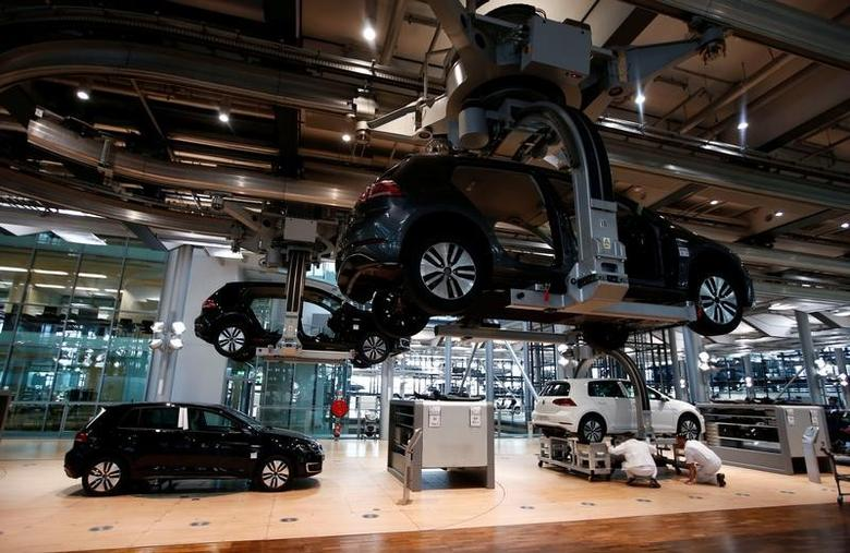 Workers assemble an e-Golf electric car at the new production line of the Transparent Factory of German carmaker Volkswagen in Dresden, Germany March 30, 2017. REUTERS/Fabrizio Bensch