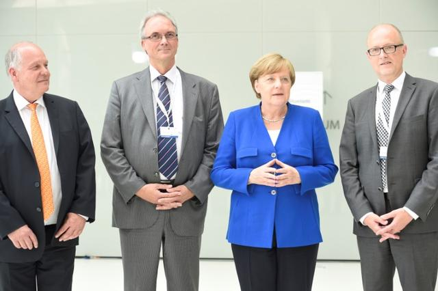German Chancellor Angela Merkel is welcomed by Walter Pelka, Ernst-Christoph Stolper and Bernd Bornhorst as she arrives at the Civil20 summit, which brings together civil society organisations from over 50 countries to discuss its recommendations to the G20, in Hamburg, Germany, June 19, 2017. REUTERS/Fabian Bimmer