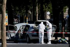 Members of the scientific police inspect a burned car at the scene of an incident in which a car rammed a gendarmerie van on the Champs-Elysees Avenue in Paris, France, June 19, 2017. REUTERS/Gonzalo Fuentes