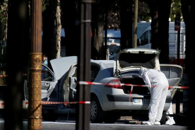A member of the scientific police inspects a burned car at the scene of an incident in which a car rammed a gendarmerie van on the Champs-Elysees Avenue in Paris, France, June 19, 2017. REUTERS/Gonzalo Fuentes