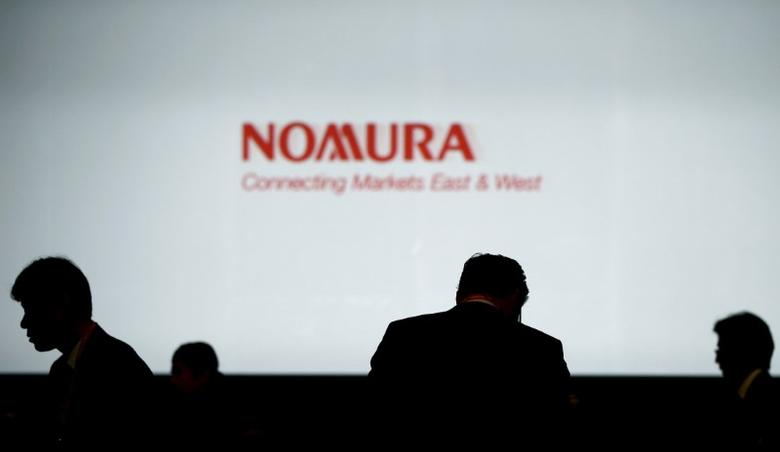 FILE PHOTO: Investors stand in front of a screen showing the logo of Nomura Holdings in Tokyo, Japan, in this December 1, 2015 file photo.  REUTERS/Toru Hanai/Files