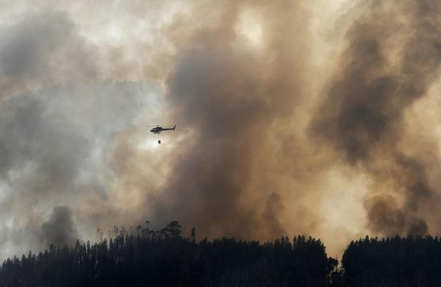 A firefighting helicopter dumps water on a forest fire in Mendeira, Portugal June 19, 2017. REUTERS/Miguel Vidal