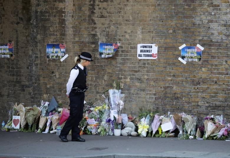 A police officer stands in front of messages and tributes left near to where a van was driven at muslims in Finsbury Park, North London, Britain, June 19, 2017. REUTERS/Kevin Coombs