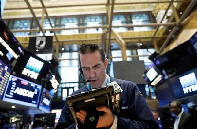 6月19日、米国株式市場は上昇し、ダウ工業株30種とS&P総合500種は終値で過去最高値を更新した。ニューヨーク連銀のダドリー総裁の発言で米経済への楽観的な見方が広がり、ハイテクなどの成長株に買いが入った。写真はニューヨーク証券取引所、5月撮影(2017年 ロイター/Brendan McDermid)