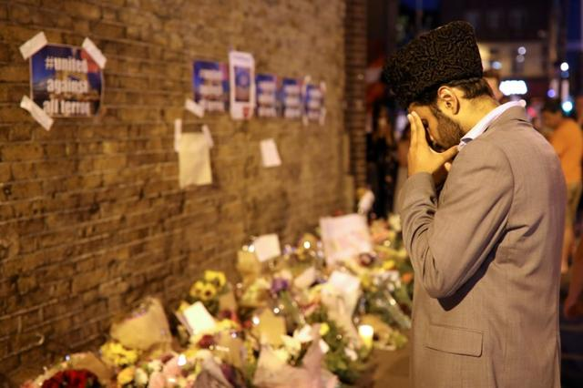 A man prays in front of messages and tributes left near to where a van was driven at Muslims in Finsbury Park, North London, Britain, June 19, 2017. REUTERS/Marko Djurica