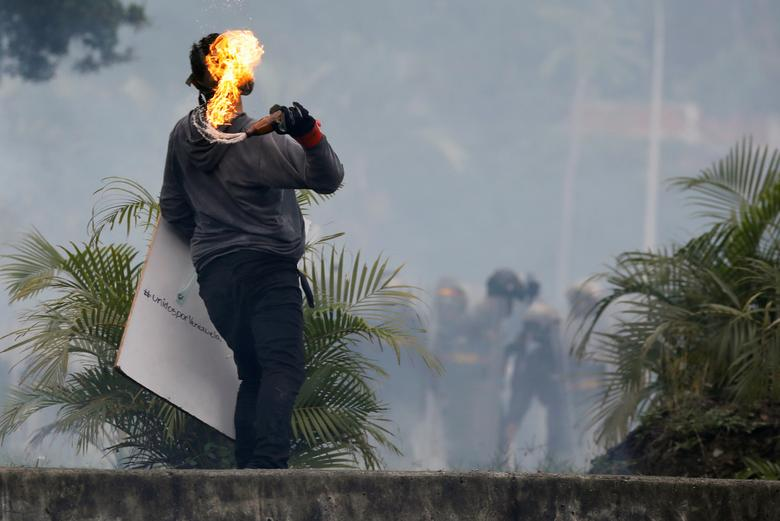 A demonstrator throws a molotov cocktail during a clash with riot security forces at rally against Venezuela's President Nicolas Maduro's government in Caracas, Venezuela, June 19, 2017. REUTERS/Carlos Garcia Rawlins