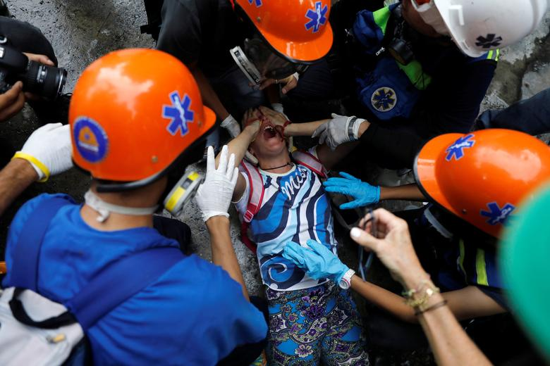 An injured demonstrator is assisted by volunteer members of a primary care response team during a rally against Venezuela's President Nicolas Maduro's government in Caracas, Venezuela, June 19, 2017. REUTERS/Carlos Garcia Rawlins
