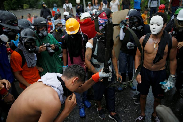 Demonstrators destroy a weapon pulled off from riot security forces while rallying against Venezuela's President Nicolas Maduro's government in Caracas, Venezuela, June 19, 2017. REUTERS/Ivan Alvarado
