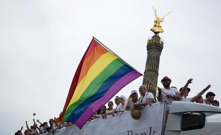 People dance in front of the Victory column as they participate in the annual Gay Pride parade, also called Christopher Street Day parade (CSD), in Berlin, Germany July 23, 2016. REUTERS/Stefanie Loos