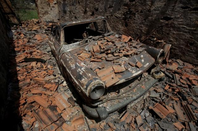 A burned out car is seen during a forest fire in Castanheira de Pera, Portugal, June 20, 2017. REUTERS/Miguel Vidal