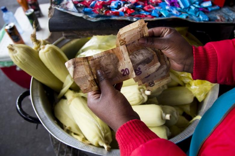 A street trader counts out change for a customer in Durban, September 8, 2015. REUTERS/Rogan Ward
