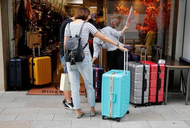 6月21日、政府観光局(JNTO)が21日に発表した5月の訪日外国人客数(推計値)は、前年同月比21.2%増の229万4700人だった。4月の23.9%増から伸び率は鈍化した。写真は銀座で買い物をする中国人観光客。昨年10月撮影(2017年 ロイター/Toru Hanai)