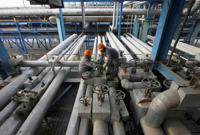 Employees close a valve of a pipe at a PetroChina refinery in Lanzhou, Gansu province January 7, 2011. Stringer