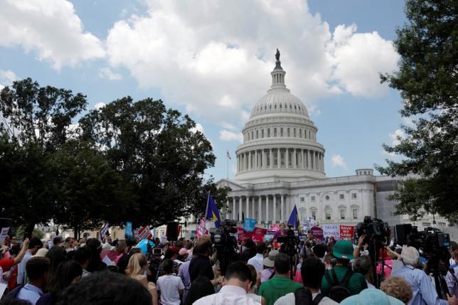 6月21日、米上院の共和党が22日に公表予定のオバマケア代替法案の草案では、オバマケアで拡大されたメディケイド(低所得者向け公的医療保険)の対象の縮小などの見直しが含まれるとみられる。写真は21日、ワシントンで共和党によるオバマケア代替法案に抗議する人々(2017年 ロイター/Aaron P. Bernstein)