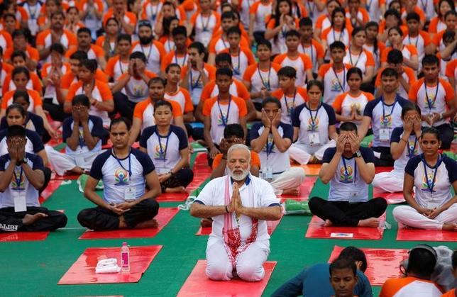 6月21日、「国際ヨガの日」を祝し、インド北部のラクナウでは、あいにくの雨模様にもかかわらず、モディ首相(写真中央)とともに約5万人が戸外でのヨガセッションに参加した(2017年 ロイター/Pawan Kumar)