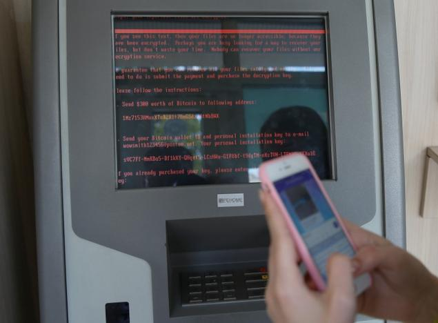 A message demanding money is seen on a monitor of a payment terminal at a branch of Ukraine's state-owned bank Oschadbank
