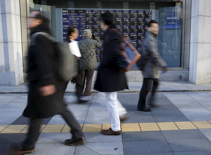 A man (3rd L) looks at an electronic stock quotation board as passers-by walk past, outside a brokerage in Tokyo, Japan January 20, 2016.  REUTERS/Toru Hanai