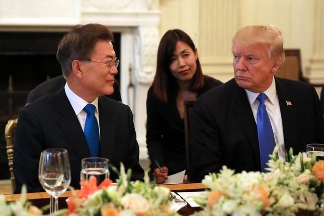 6月29日、訪米中の韓国の文在寅(ムン・ジェイン)大統領(写真左)は、トランプ大統領(同右)夫妻がホワイトハウスで主催した夕食会に出席した。両首脳の初会談では北朝鮮の核開発問題を中心に協議するほか、トランプ大統領が韓国側に自動車や鉄鋼を巡る通商問題の解消を求める見通し(2017年 ロイター/Carlos Barria)