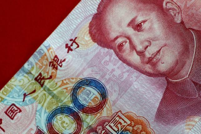 7月4日、中国人民銀行(中央銀行)は取引開始前、人民元の対ドル基準値(中間値)を1ドル=6.7889元とし、前日の基準値からは117ピップ、0.17%元安の水準に設定した。比率としては6月20日以来の大幅な元安設定。写真は人民元紙幣。シンガポールで5月撮影(2017年 ロイター/Thomas White/Illustration)