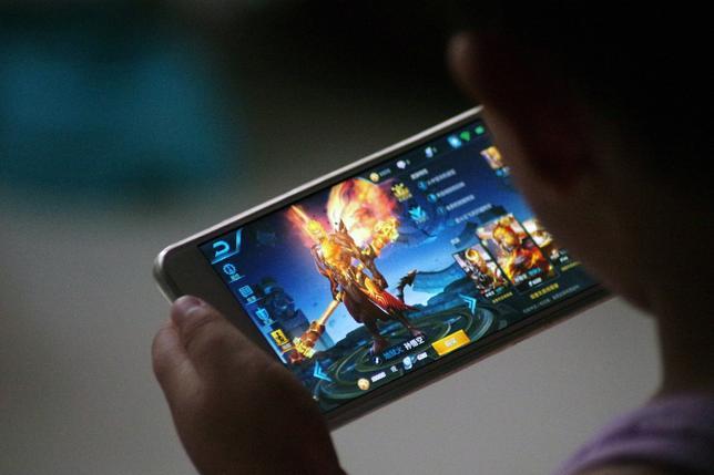 7月3日、中国ネットサービス大手の騰訊控股(テンセント・ホールディングス)が、人気モバイルゲーム「王者栄耀(オナー・オブ・キングス)」について、若年層ユーザーのプレー時間を制限すると発表した。2日、山東省で「王者栄耀」で遊ぶ子ども(2017年 ロイター)