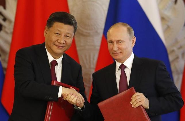 7月4日、ロシアと中国は緊張緩和への参画を北朝鮮、韓国、米国に呼び掛けた。写真はロシアのプーチン大統領(右)と中国の習近平国家主席。モスクワで同日撮影(2017年 ロイター/Sergei Karpukhin)